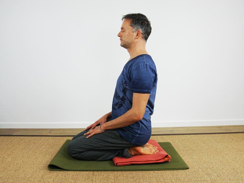Yoga Sitzhaltung Vajrasana mit decke als Unterstützung - Meditationssitz